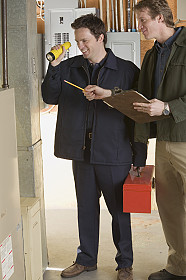 Electricians inspecting circuit breakers